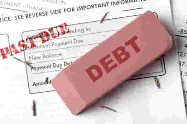 "Debt relief concept. An eraser with the word ""DEBT"" on it erasing past due bills."