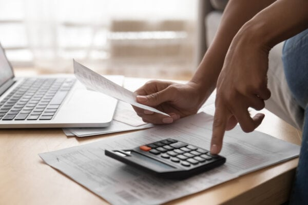 Person using calculator to solve Debt challenges