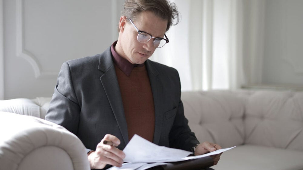 man looking over papers for a plan for paying off his debt