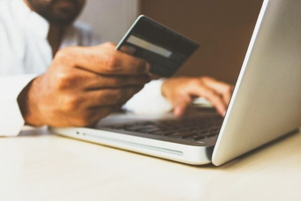 man in debt on his laptop while holding his credit card