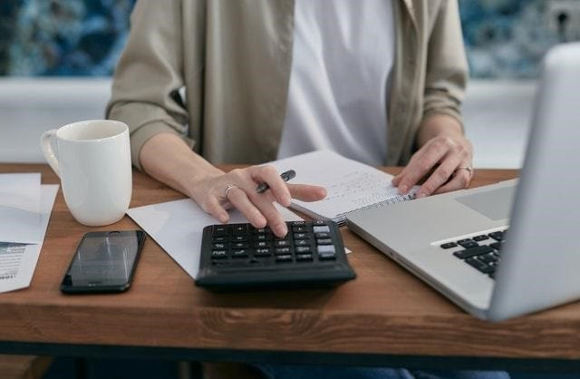 woman calculating her tax debt using a calculator