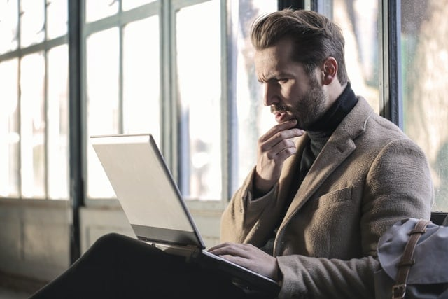 man thinking about payment deferral programs on his laptop